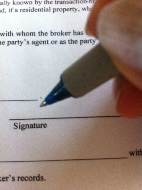 Person getting ready to sign a document