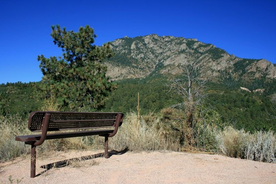 Cheyenne Mountain in background with metal bench in foreground
