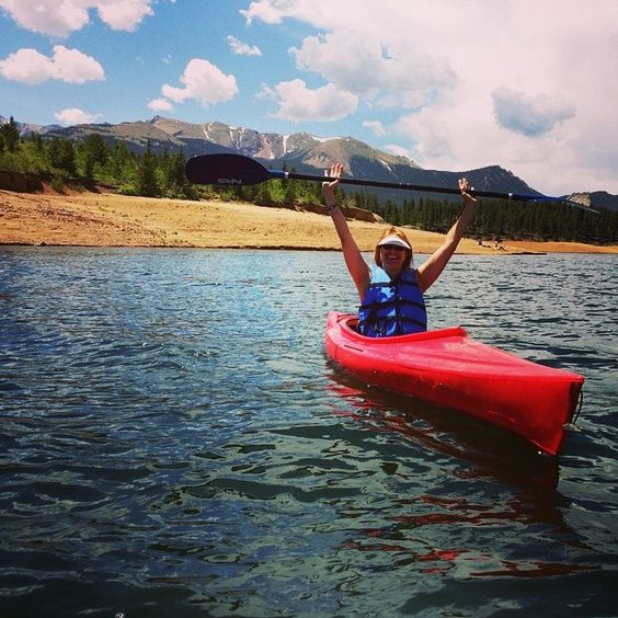 Picture of a woman kayaking on a reservoir in Colorado with trees & mountains in the background