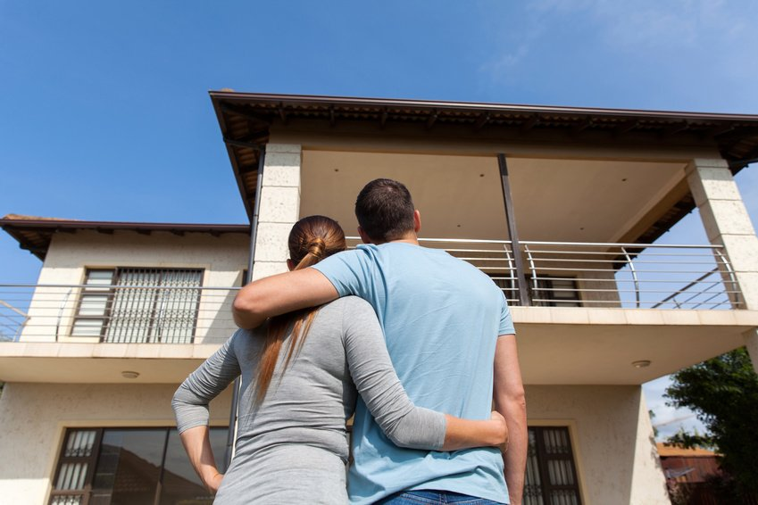 Picture of a young couple standing with their arms around each other with their backs to the camera staring at their new house
