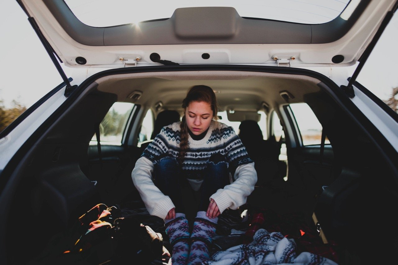 Girl in back of car with warm clothes on