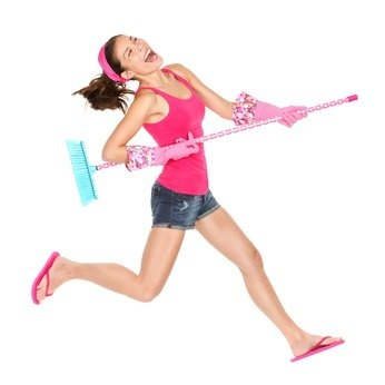 spring cleaning tips, woman jamming out with her broom dressed in hot pink top, jean shorts and pink flip flops