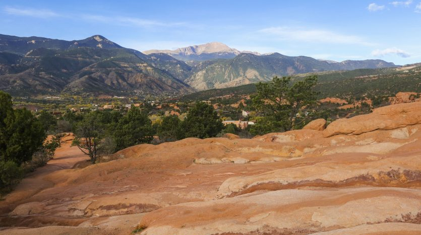 View of red rocks, trees with Pikes Peak in the background