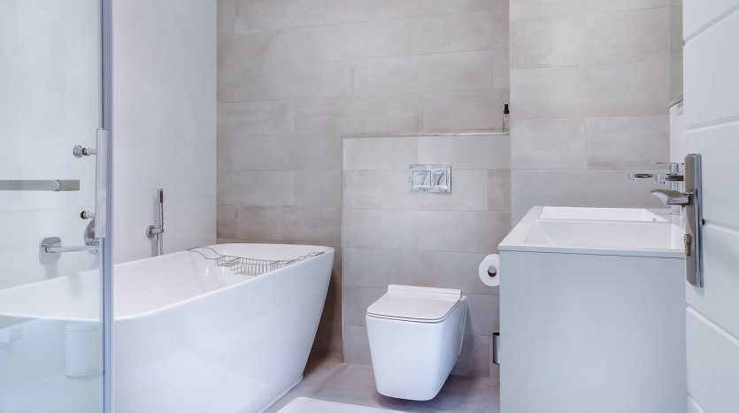 Picture of a unique bathroom with a toilet, free standing tub and sink cabinet