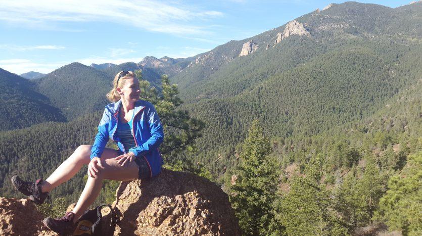 Susanna Haynie sitting on a rock during a mountain hike