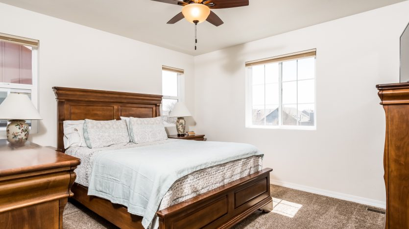 Picture of a master bedroom with a white cover on the bed