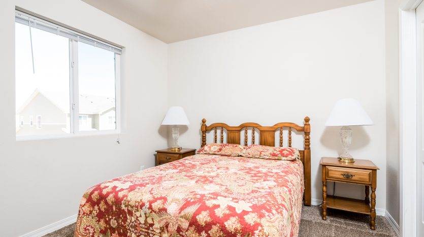 Picture of a bedroom with a paisley flowered bedspread, nightstands flank each side of the bed