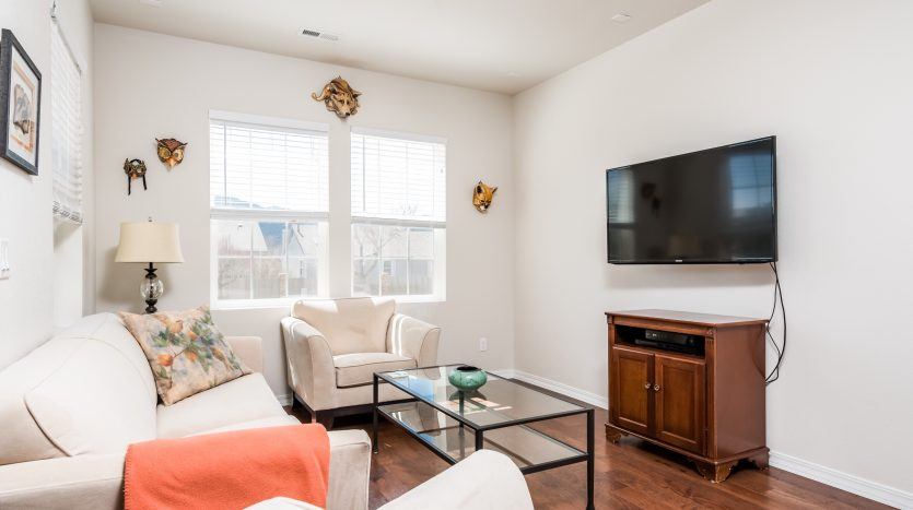 A predominantly white living room with natural light, a TV is mounted on the wall