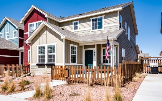 Front exterior of a tan painted townhome for sale entrance with brown picket fence and American flag