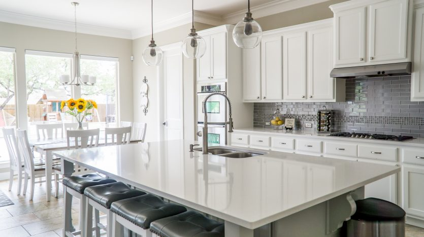 All white kitchen with accents of gray and bright yellow