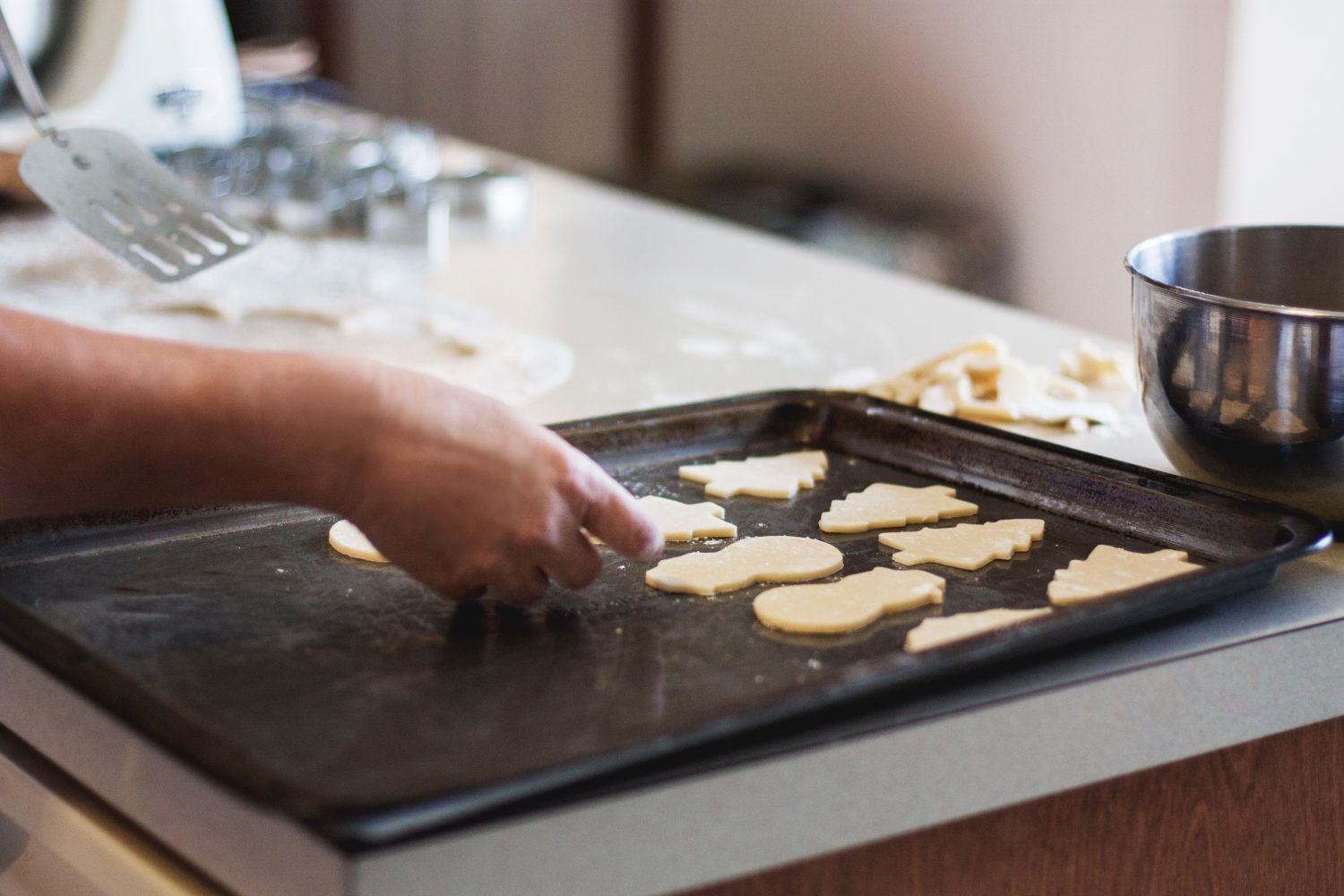 Person putting Christmas cookies on baking sheet