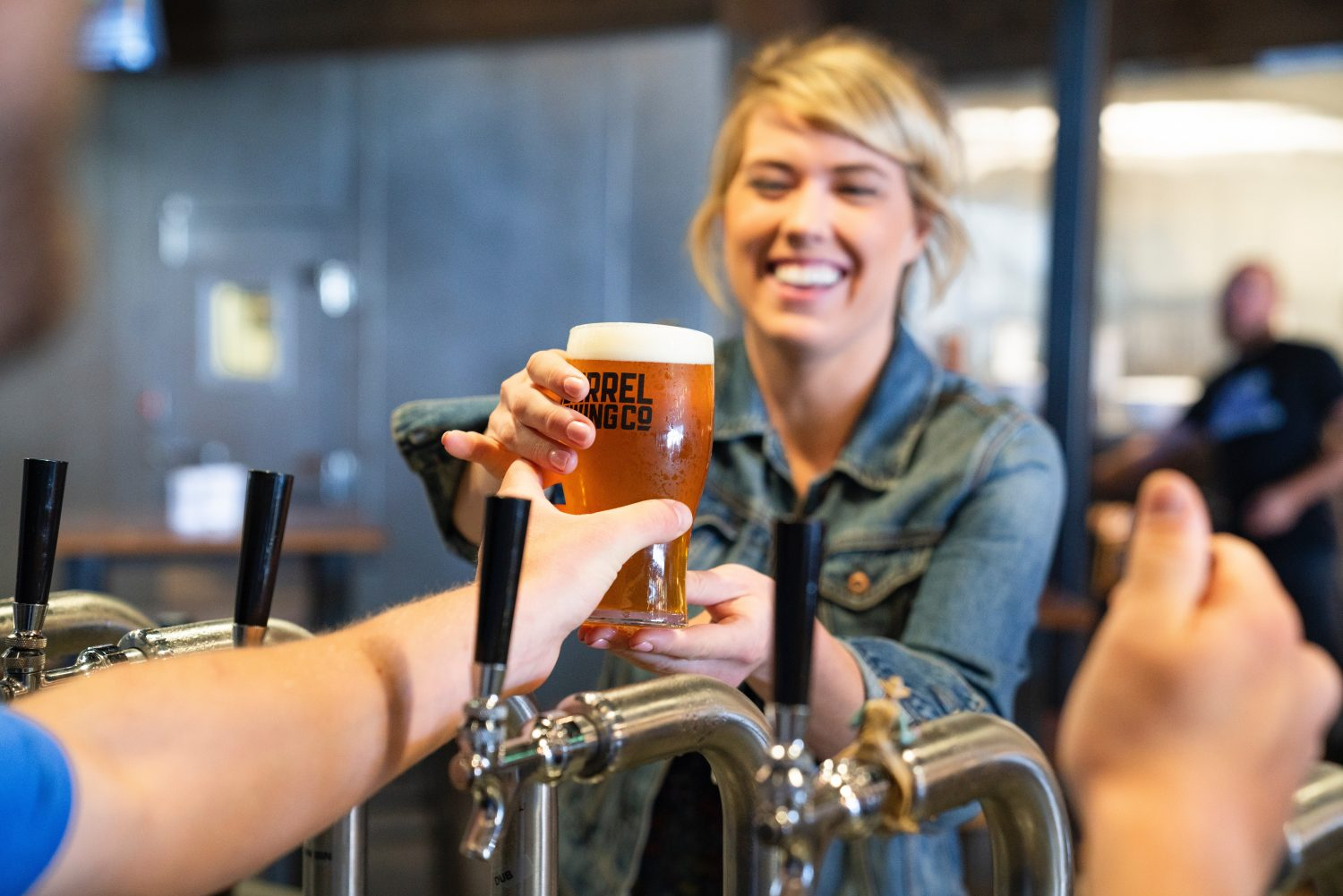 Picture of person handing woman a beer