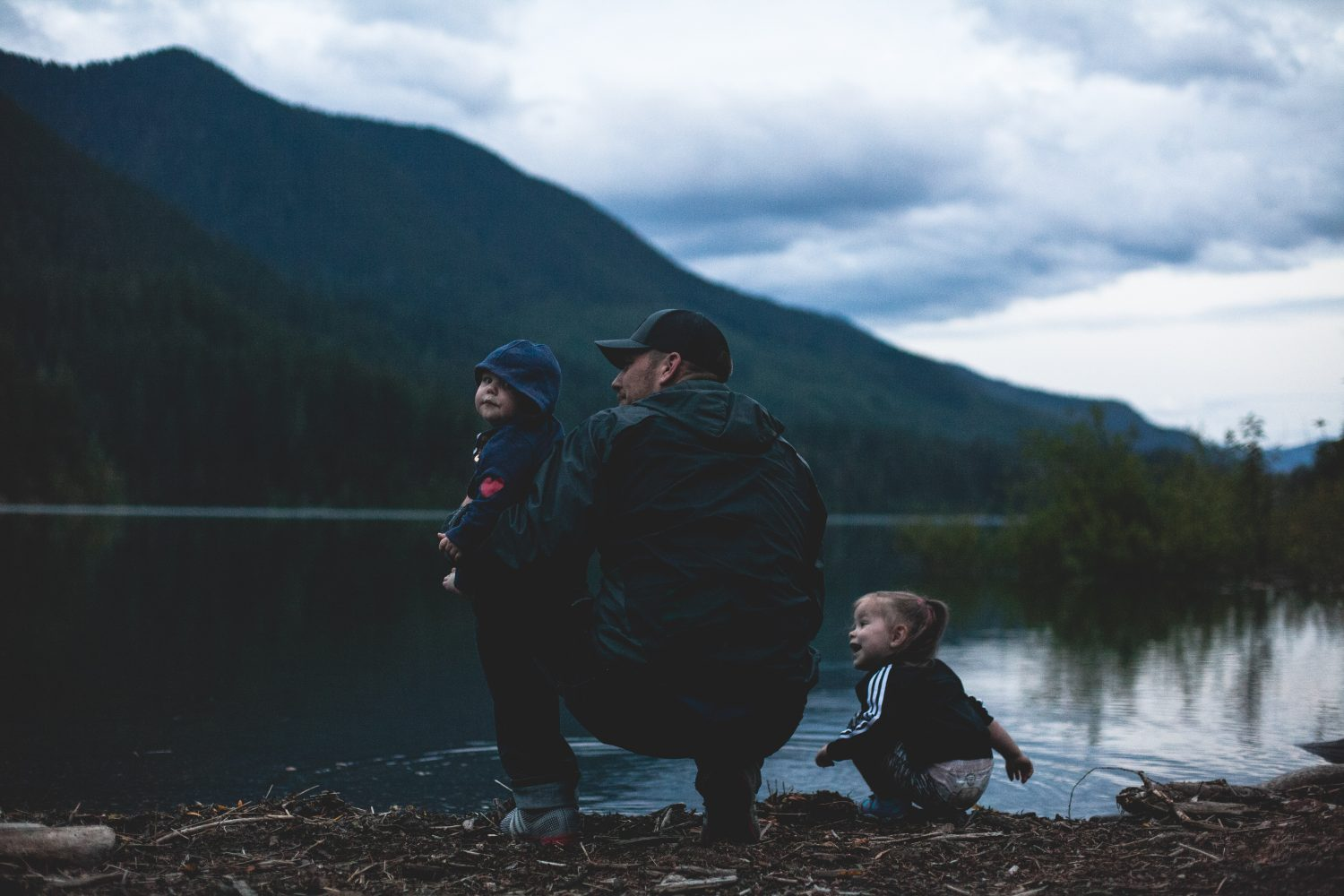 Man with two children near a lake with a mountain