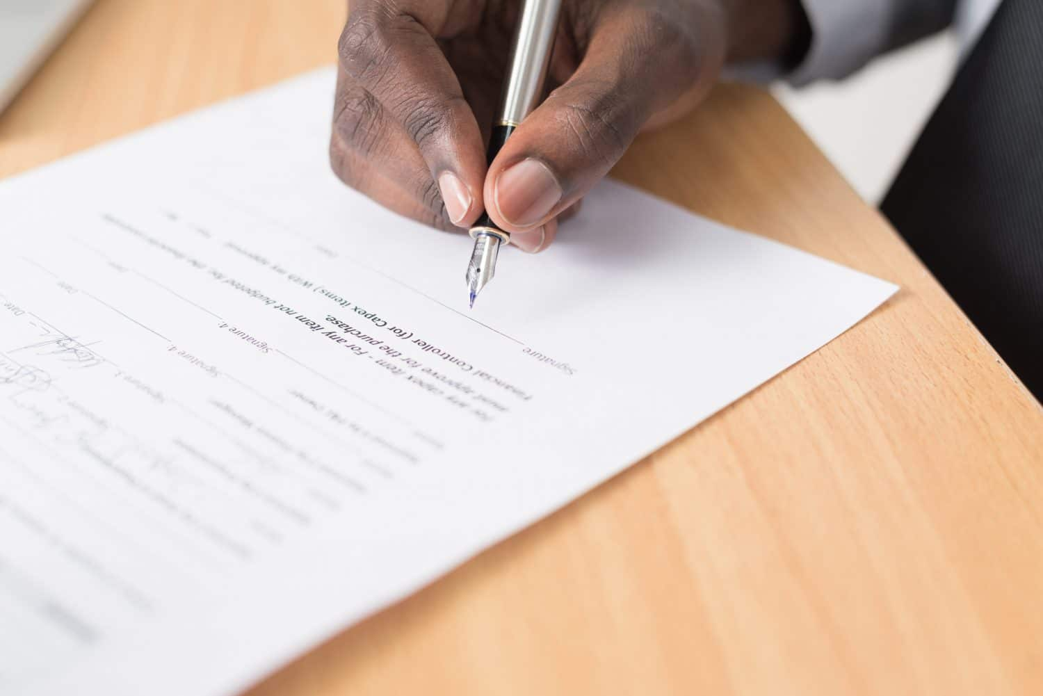 picture of a hand holding a pen about to sign paperwork