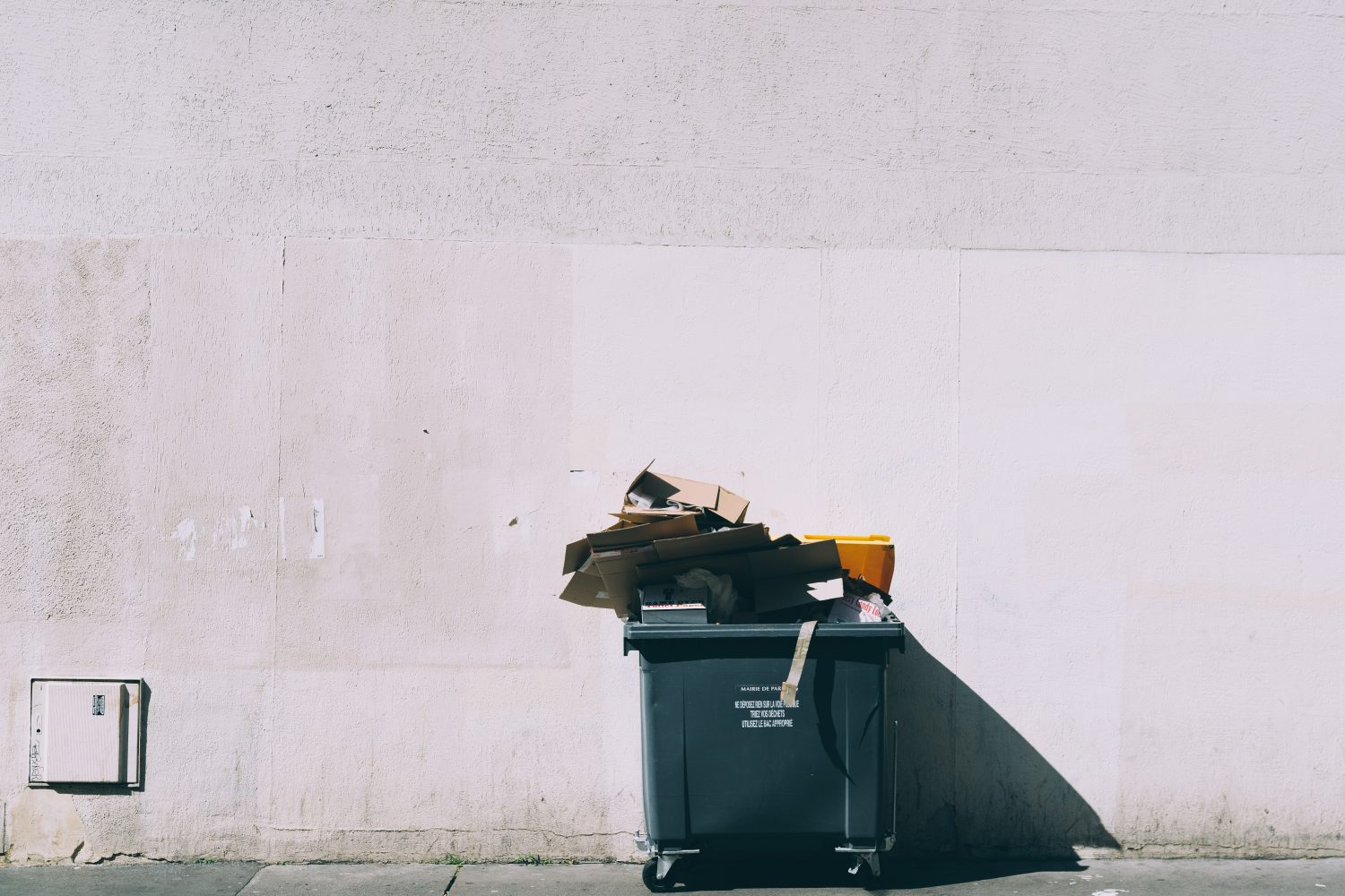 photo of overflowing trash bin in front of white building