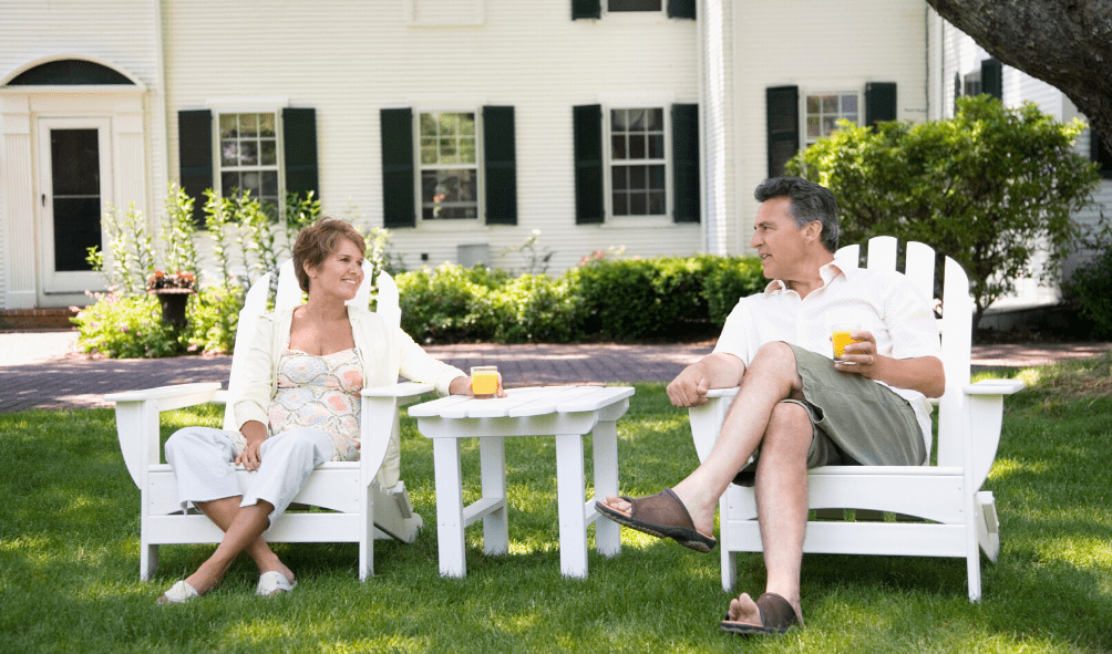 picture of man and woman sitting in chairs in front of house