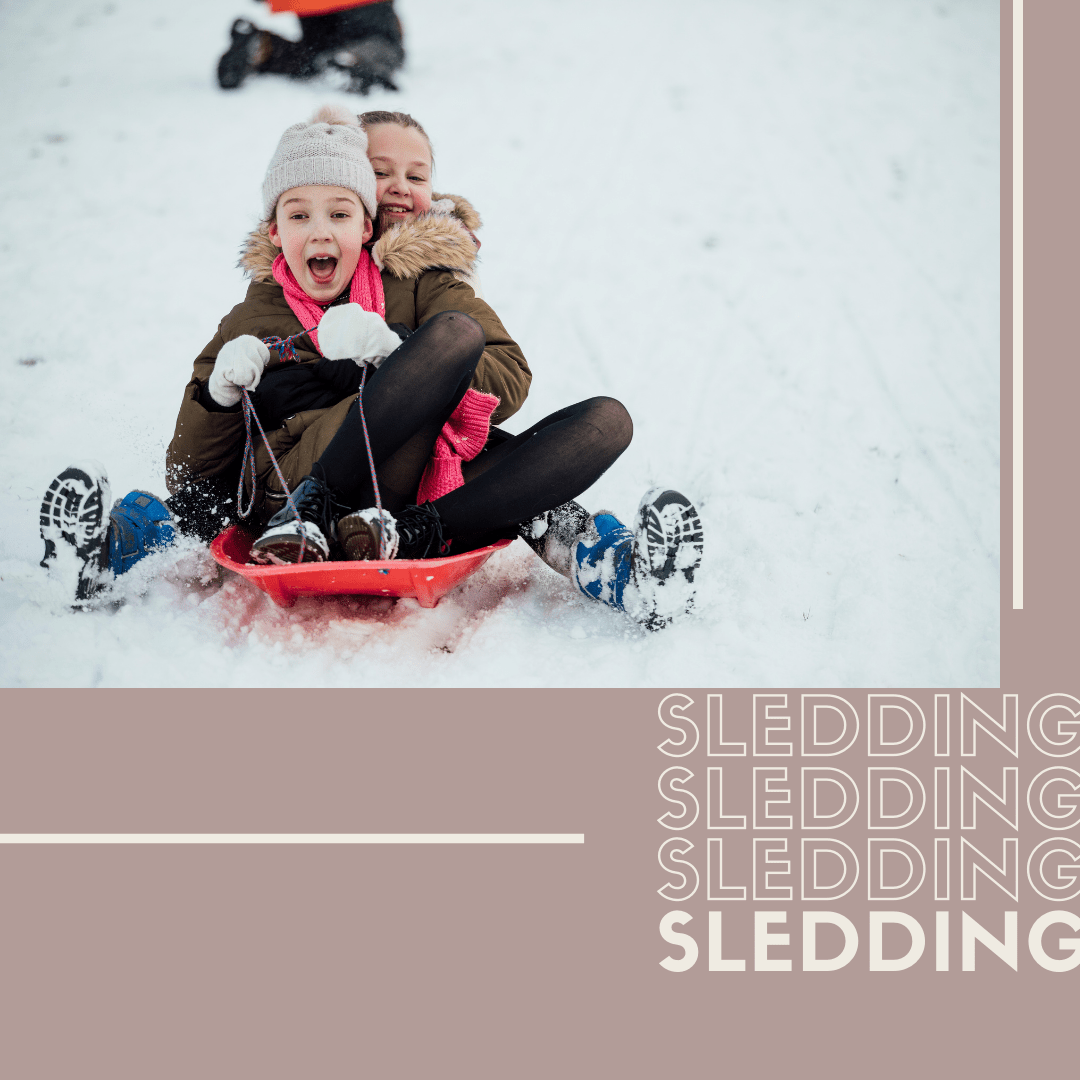 picture of two girls sledding down a snowy hill