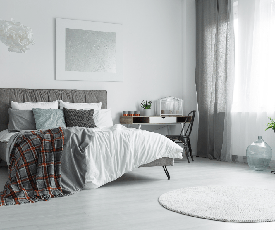photo of bedroom with white and gray linens and curtains