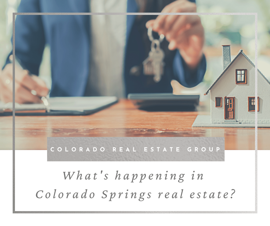 """picture of professional holding keys at conference table with house and caption """"what's happening in Colorado Springs real estate?"""""""